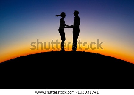 silhouette of couple on hill in sunset - stock photo