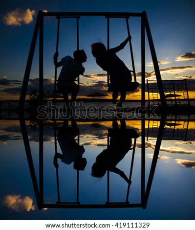 silhouette of couple. synchronous swinging on a swing and kissing in the evening on the background of a dramatic sunset sky. man and woman in love