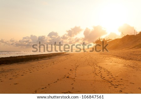 Silhouette of couple taking a walk on beach in sunset - stock photo