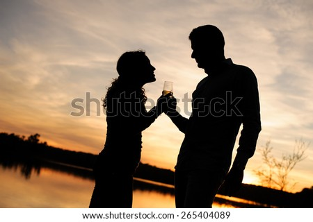 Silhouette of couple toasting at sunset