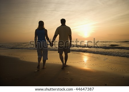 Silhouette of couple walking on beach at sunset holding hands. Horizontally framed shot. - stock photo
