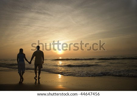 Silhouette of couple walking on beach at sunset holding hands. Horizontally framed shot.