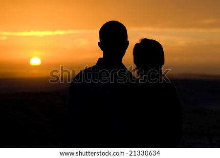 Silhouette of couple watching sunset - stock photo