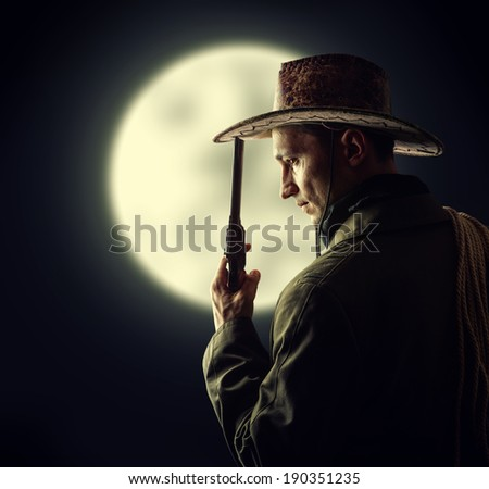 silhouette of cowboy holding hat and revolver outdoor. Full moon - stock photo