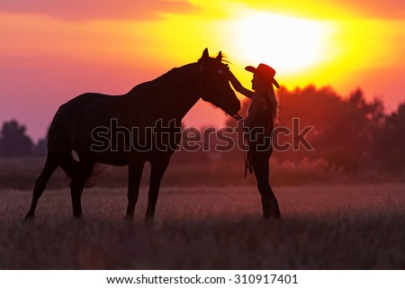 Silhouette of cowgirl and a horse - stock photo