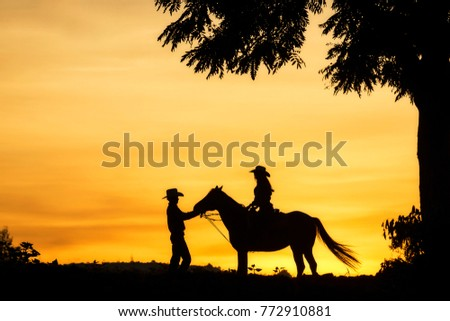 Silhouette of cowgirl and cowboy riding a horse.