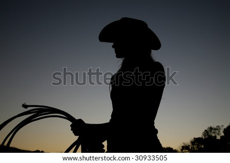 Silhouette of Cowgirl with Rope - stock photo