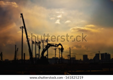 Silhouette of crane and electricity pylons - stock photo