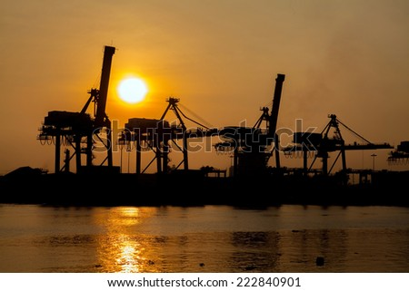 Silhouette of crane in shipyard at sunset time - stock photo