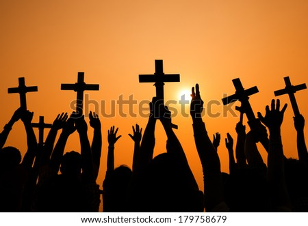 Silhouette of Crosses Held Up at Sunset - stock photo
