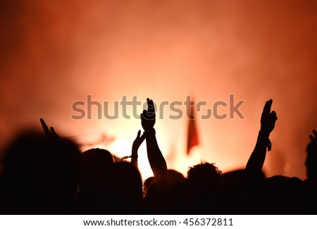 Silhouette of crowd. Audience with hands raised at a music festival