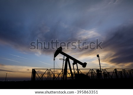 Silhouette of crude oil pump and cloudy sunset in the oil field. - stock photo