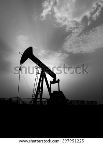 Silhouette of Crude oil pump and cloudy sunset in the oil field- Black and white