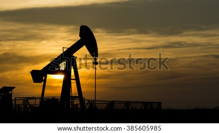 Silhouette of crude oil pump at cloudy sunset in oil field. - stock photo