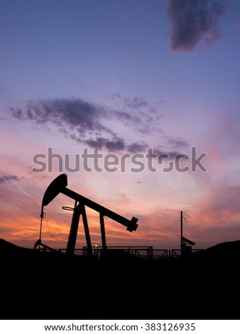 Silhouette of crude oil pump in oil field at sunset.