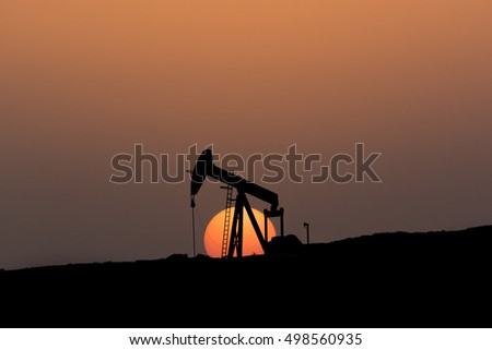 Silhouette of crude oil pump in oil field at sunset