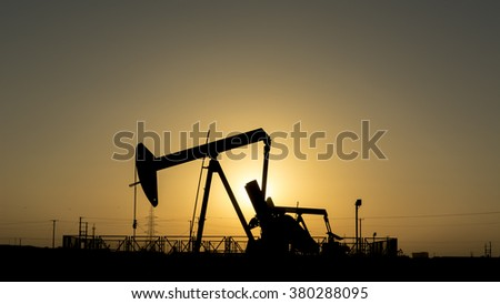 Silhouette of crude oil pump in the oil field at sunset  - stock photo