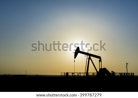 silhouette of crude oil pump unit at sunset in oil field