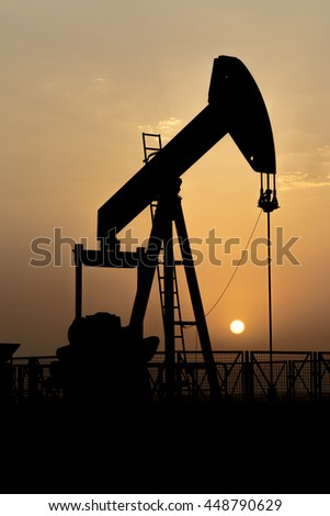 Silhouette of crude oil pumping unit  in oil field at sunset - BPU pump unit