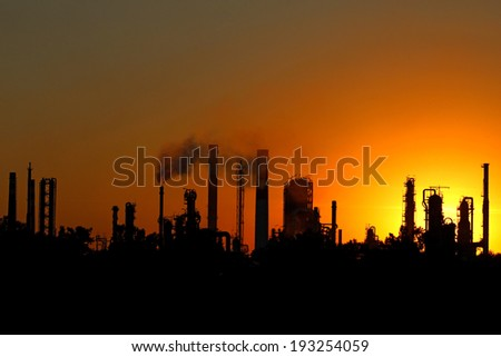 silhouette  of crude oil refinery during sunset - stock photo