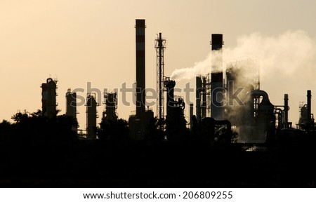 silhouette  of crude oil refinery station during dusk - stock photo