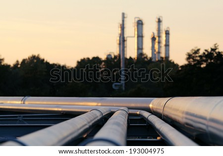 silhouette  of crude oil refinery station during sunset with long pipes - stock photo
