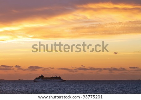 Silhouette of cruise ship at sunset in a sea - stock photo