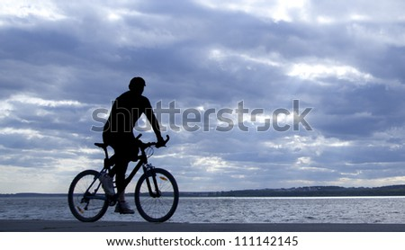 silhouette of cyclist in motion on the background of a beautiful blue sky
