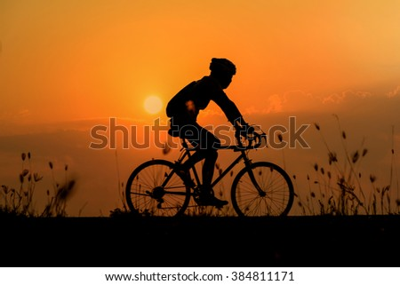 Silhouette of cyclist on beautiful sky ,Man cyclist start on hill in park ,Man ride bicycle on sunset background