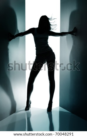 Silhouette of  dancing girl between black curtains - stock photo