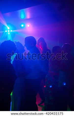 Silhouette of dancing people in night club under the light