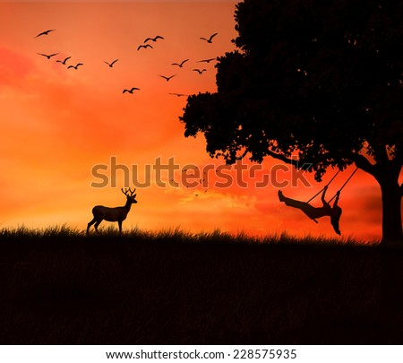 Silhouette of deer and happy young woman on a swing of tree isolated on beautiful sunset evening dusk sky background. Body vitality, human spirit well being, freedom, happiness, joy nature concept - stock photo