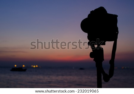 Silhouette of digital camera on tripod with sunset sky at sea blured background - stock photo