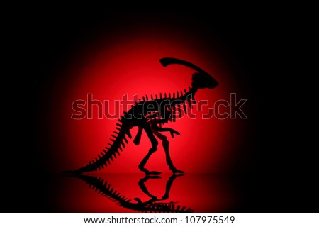 Silhouette of dinosaur on black with reflection. - stock photo