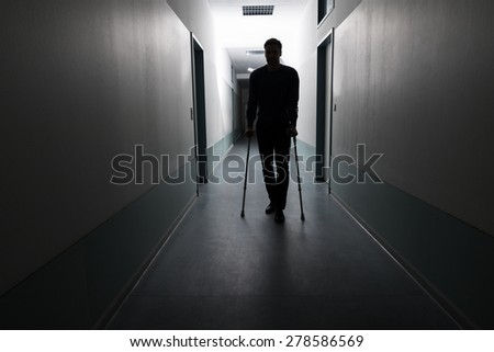 Silhouette Of Disabled Man Walking With Crutches In Hospital - stock photo