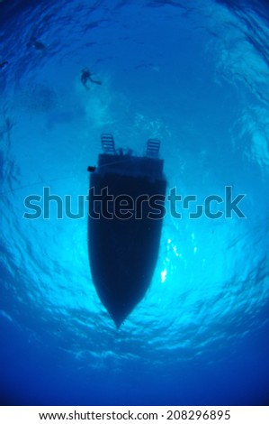 Silhouette of divers on surface with dive boat, Grand Cayman - stock photo