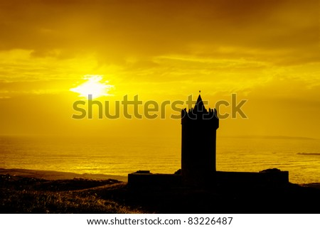 Silhouette of Doonagore castle at sunset in Ireland. - stock photo