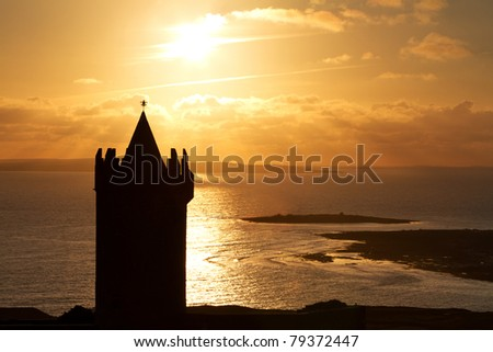 Silhouette of Doonagore castle at sunset - Ireland - stock photo
