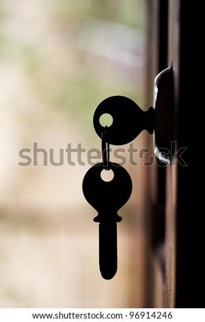 Silhouette of door keys hanging on the open door with blurred background - stock photo
