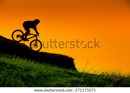 silhouette of downhill mountain bike ride at sunset - stock photo