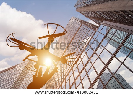 silhouette of drone concept in the city - stock photo