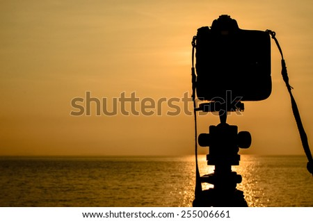 Silhouette of DSLR camera with sea at sunrise, Photo at morning time concept - stock photo