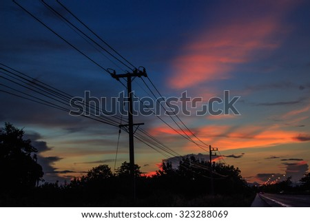 silhouette of electric post and wires in the background of twilight sky.