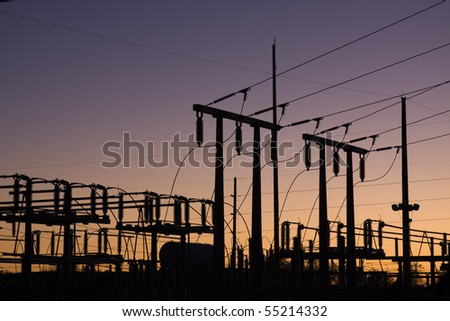 Silhouette of electric power lines and power station at sunset - stock photo
