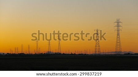 Silhouette of electrical power transmission pylons under sunset golden sky. The photo was taken at Baylands Nature Preserve in Palo Alto, California, by the south end of the San Francisco Bay. - stock photo