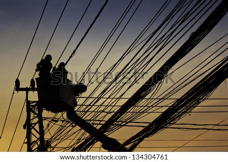 silhouette of electrician and cable - stock photo
