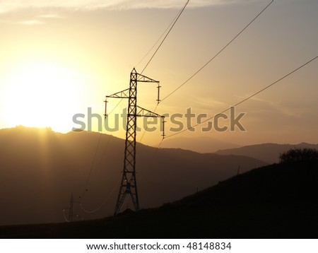 silhouette of electricity pylon and cables at the sunset on the ridge of mountains - stock photo