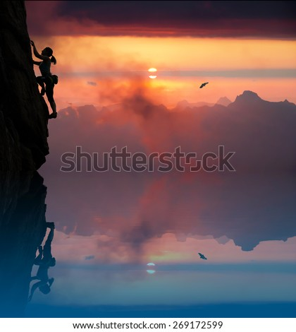 Silhouette of elegant female climber with lake and dusk. Slim woman athlete ascending rock wall above blue lake mountains and vivid red sunset on the background - stock photo