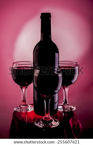 Silhouette of Elegant red three wine glass around alone full bottle with cork in  vinous background with white spot in center  - stock photo