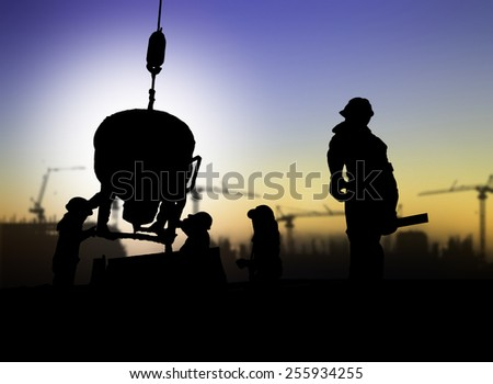 silhouette of engineer and construction worker on scaffold in a building site over Blurred construction site - stock photo